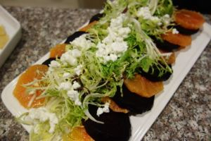 Salad of frisée on a bed of beets and oranges