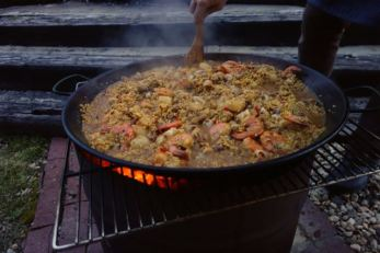 Cooking paella over a fire barrel in the back yard