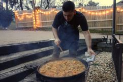 cooking paella outdoors over a fire.