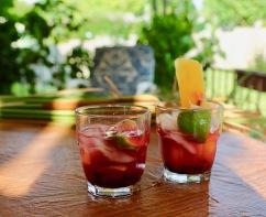 Blueberry Caipirinhas, one holding a fruit ice