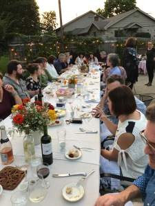 Over twenty guests seated at one long table covered in a tablecloth and set for dinner