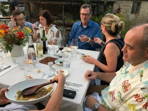 people at a long table passing an oval dish of cooked bitter mellon