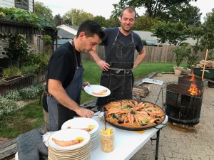 two chefs putting paella on plates