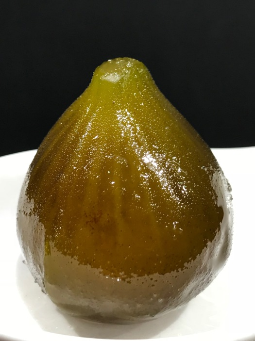 A candied unripe fig resting on a white spoon glistens with sugar syrup